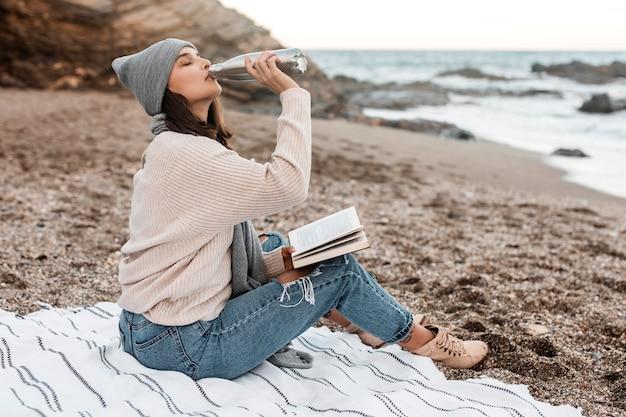 Widok z boku kobiety na plaży, pije i czyta książkę