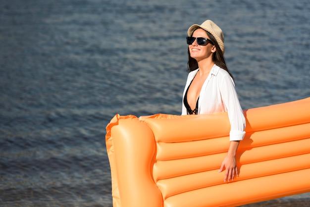 Widok z boku kobiety na plaży z nadmuchiwanym materacem