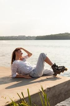 Widok z boku kobiety na rolkach podziwiająca widok na jezioro