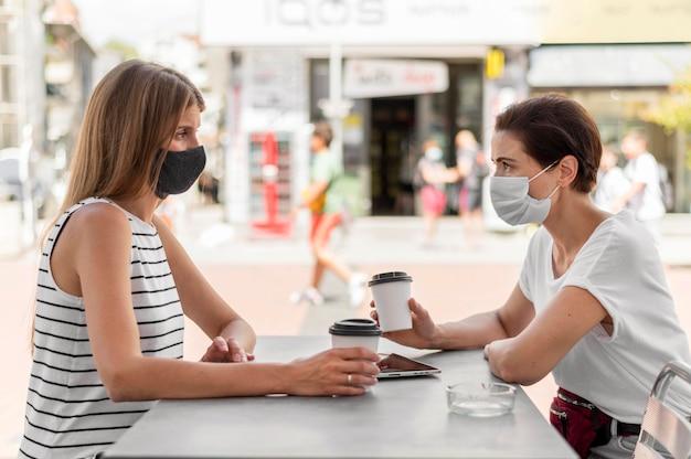 Widok z boku kobiety na tarasie z maskami