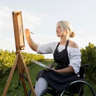 Widok z boku kobiety na wózku inwalidzkim na zewnątrz w przyrodzie z płótna i palety