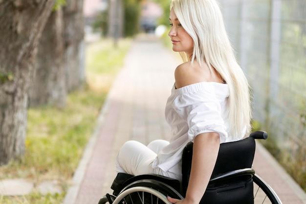 Widok z boku kobiety na wózku inwalidzkim na zewnątrz z miejsca na kopię