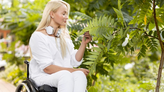 Widok z boku kobiety na wózku inwalidzkim na zewnątrz z roślin