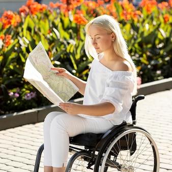 Widok z boku kobiety na wózku inwalidzkim, patrząc na mapę na zewnątrz