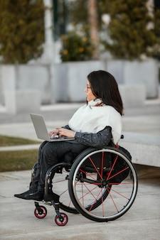 Widok z boku kobiety na wózku inwalidzkim z laptopem