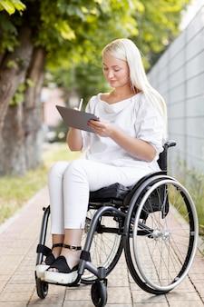 Widok z boku kobiety na wózku inwalidzkim z tabletem
