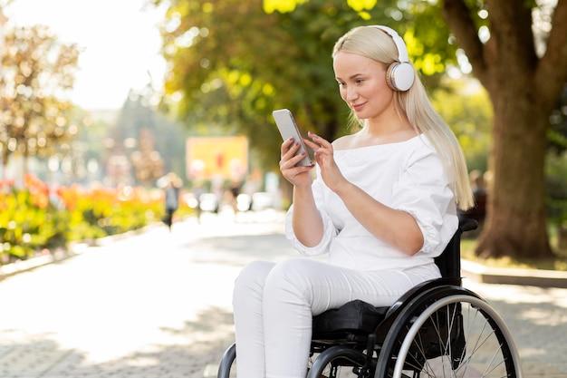 Widok z boku kobiety na wózku inwalidzkim ze smartfonem i słuchawkami