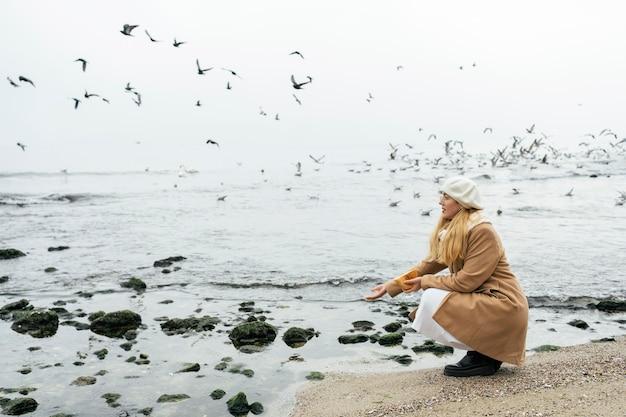 Widok z boku kobiety na zewnątrz na plaży w zimie