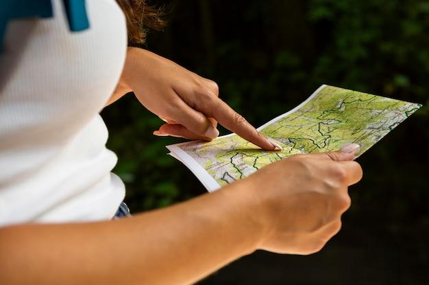 Widok z boku kobiety na zewnątrz w przyrodzie z mapą