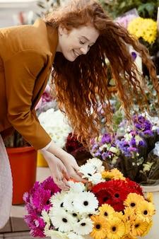 Widok z boku kobiety na zewnątrz wiosną z bukietem kwiatów