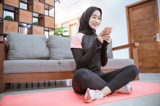 Widok z boku kobiety noszącej hidżab sportowy siedzi ze skrzyżowanymi nogami na macie do jogi podczas korzystania z telefonu komórkowego