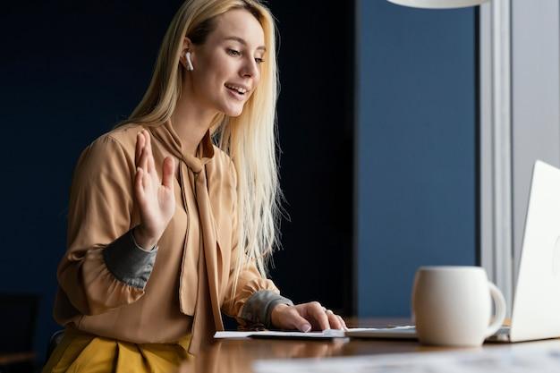 Widok z boku kobiety o rozmowie wideo w pracy