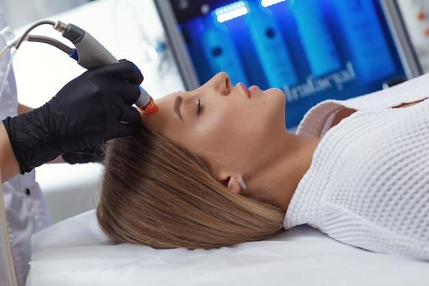 Widok z boku kobiety otrzymującej mikrodermabrazję na czole w spa. zabieg wodno-twarzowy w klinice kosmetologicznej.