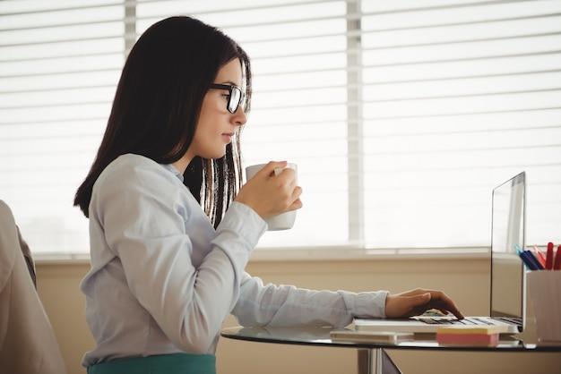Widok z boku kobiety pije kawę siedząc przy laptopie