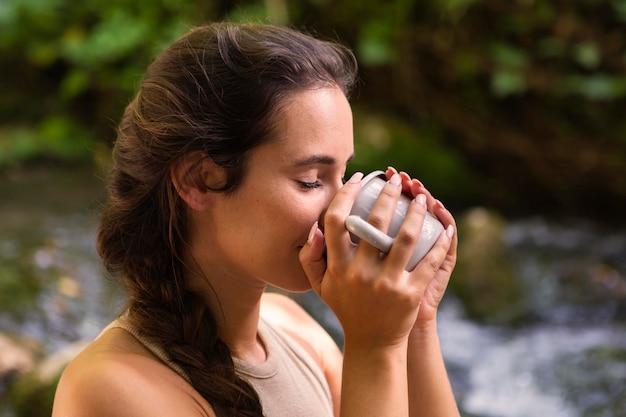Widok z boku kobiety pije z kubka, podczas gdy na zewnątrz w przyrodzie