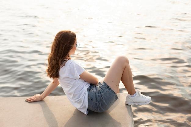 Widok z boku kobiety podziwiającej widok na jezioro
