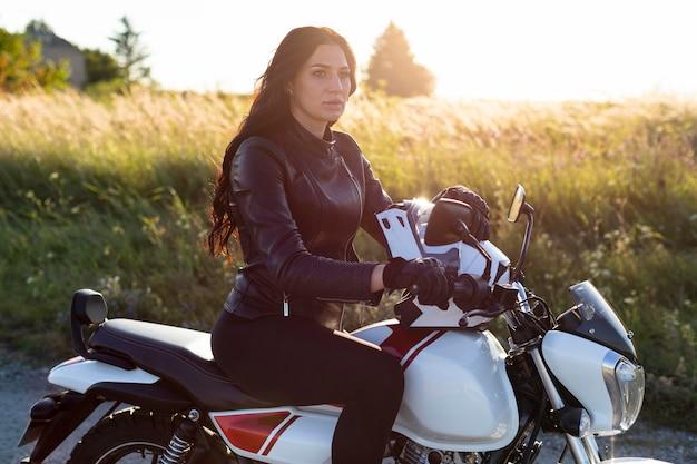 Widok z boku kobiety pozuje na motocyklu