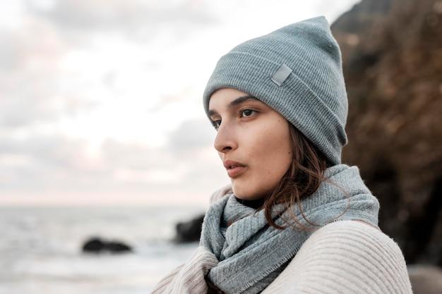 Widok z boku kobiety pozuje na plaży z miejsca na kopię