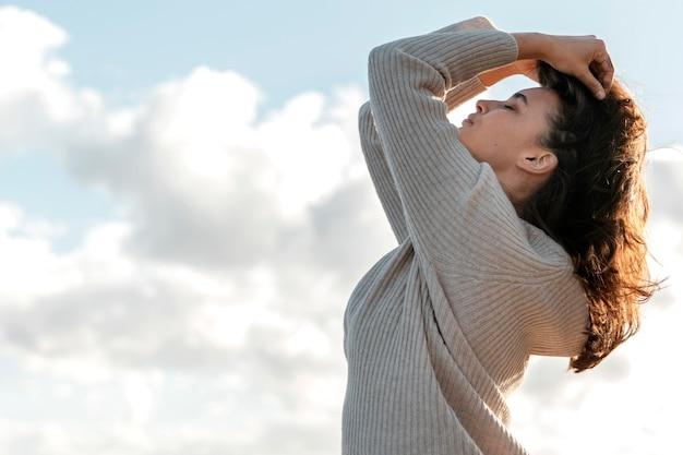 Widok z boku kobiety pozuje na tle nieba z miejsca na kopię