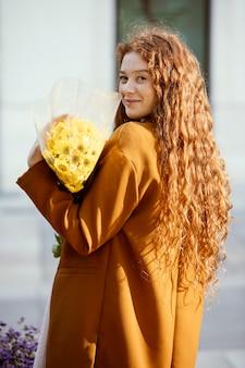 Widok z boku kobiety pozuje na zewnątrz z bukietem wiosennych kwiatów