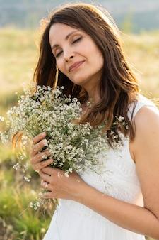 Widok z boku kobiety pozuje w przyrodzie z bukietem kwiatów