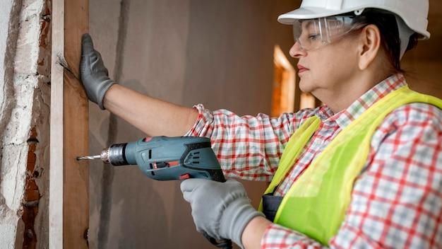 Widok z boku kobiety pracownik budowlany z hełmem i wiertarką elektryczną