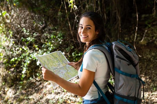 Widok z boku kobiety próbującej odkrywać przyrodę podczas korzystania z mapy