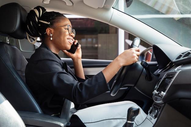 Widok z boku kobiety prowadzącej samochód i rozmawiającej jednocześnie na smartfonie