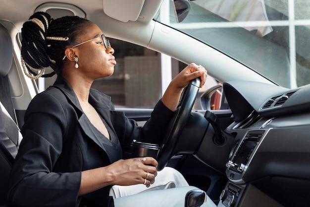 Widok z boku kobiety prowadzącej samochód trzymając filiżankę kawy
