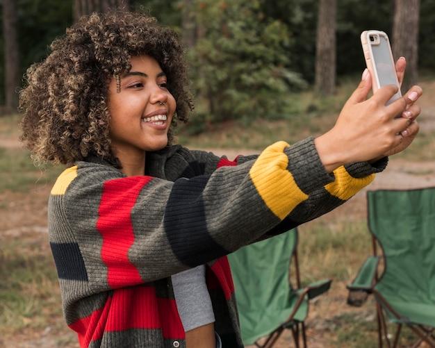 Widok z boku kobiety przy selfie podczas kempingu na świeżym powietrzu