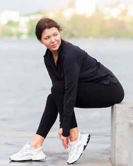 Widok z boku kobiety przygotowuje się do biegania na świeżym powietrzu