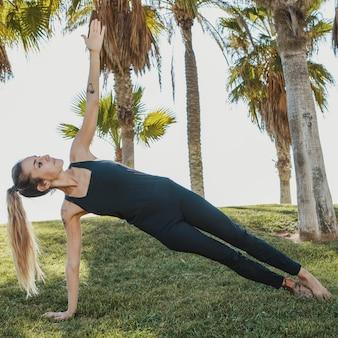 Widok z boku kobiety robi joga na trawie na zewnątrz