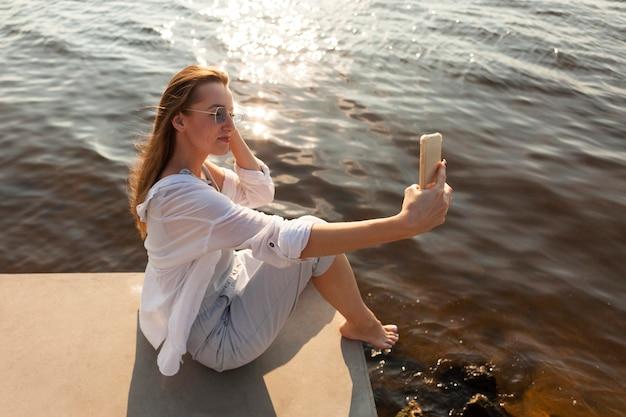 Widok z boku kobiety robiącej selfie nad jeziorem