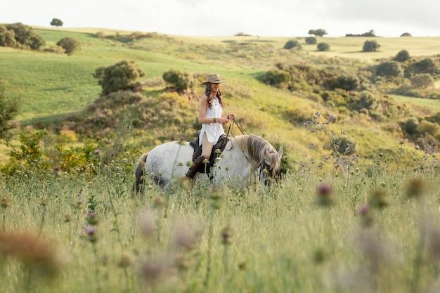 Widok z boku kobiety rolnik jazda konna w przyrodzie