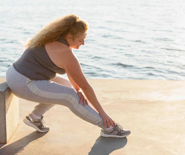 Widok z boku kobiety rozciągającej się nad jeziorem z miejsca na kopię