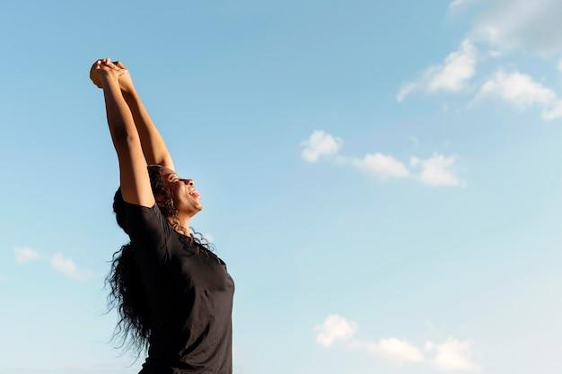 Widok z boku kobiety rozciągającej się z miejsca na kopię i bezchmurnego nieba