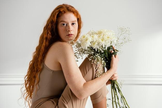 Widok z boku kobiety siedzącej i pozującej z wiosennych kwiatów