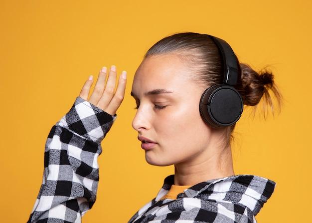 Widok z boku kobiety słuchania muzyki na słuchawkach