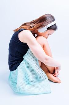 Widok z boku kobiety sobie letnie ubrania słuchania muzyki przygnębiony, siedząc na podłodze ze słuchawkami na białym tle.