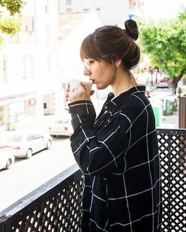 Widok z boku kobiety stoj? cej w balkonie picia kawy