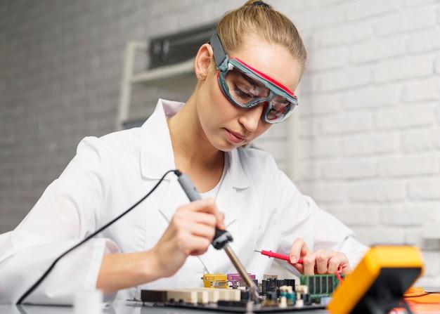 Widok z boku kobiety technika z lutownicą i płytą główną elektroniki