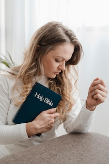 Widok z boku kobiety trzymającej biblię w domu