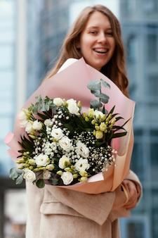 Widok z boku kobiety trzymającej bukiet kwiatów na zewnątrz