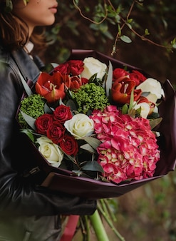 Widok z boku kobiety trzymającej bukiet róż w kolorze białym i czerwonym z czerwonymi tulipanami w kolorze różowym, hortensją i tchawicą