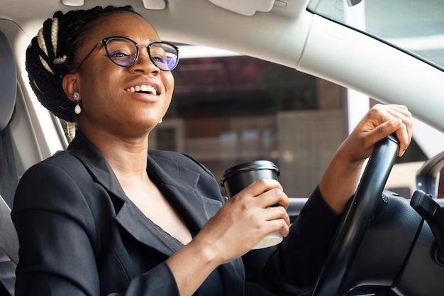 Widok z boku kobiety trzymającej filiżankę kawy w swoim samochodzie