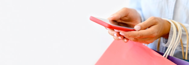 Widok z boku kobiety trzymającej smartfon i torby na zakupy na cyber poniedziałek