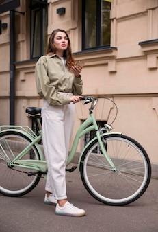 Widok z boku kobiety trzymającej smartfon siedząc na swoim rowerze