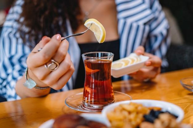 Widok z boku kobiety umieszczającej plasterek cytryny w szklance armudu z czarną herbatą