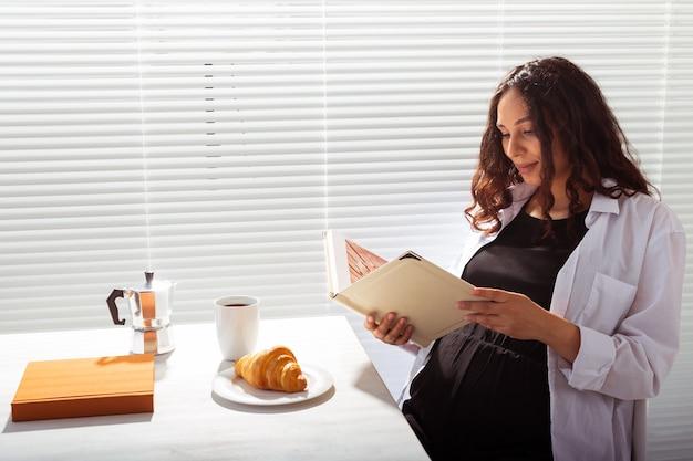 Widok z boku kobiety w ciąży, czytanie książki jedząc poranne śniadanie