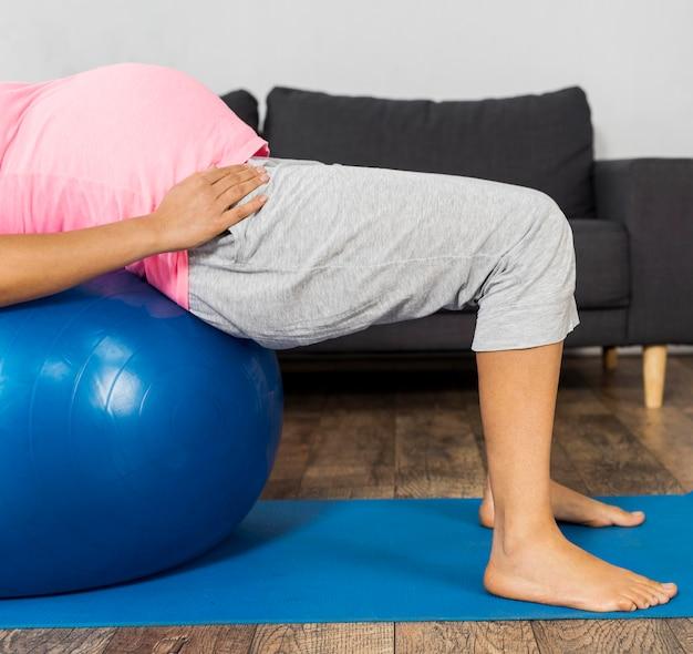 Widok z boku kobiety w ciąży za pomocą piłki do ćwiczeń do treningu